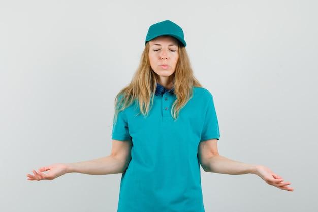 Женщина-доставщик в футболке, кепке раскидывает ладони с закрытыми глазами и смотрит с надеждой Бесплатные Фотографии