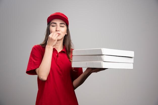 ピザの上においしいサインを作る配達の女性。 無料写真