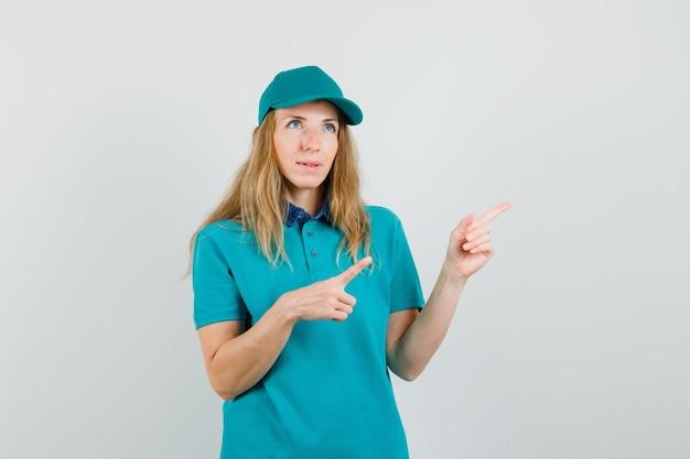 Donna di consegna che indica lontano in maglietta, berretto e guardando pensieroso Foto Gratuite