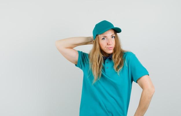 Tシャツ、帽子で頭の後ろに手を押しながらポーズをとってエレガントな配達の女性 無料写真