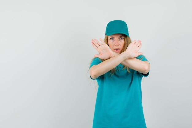 Женщина-доставщик показывает жест отказа в футболке, кепке и выглядит серьезно Бесплатные Фотографии
