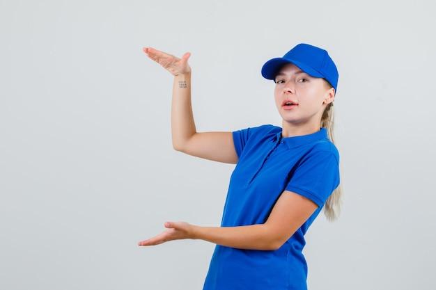 Женщина-доставщик показывает знак размера в синей футболке и кепке и выглядит уверенно Бесплатные Фотографии