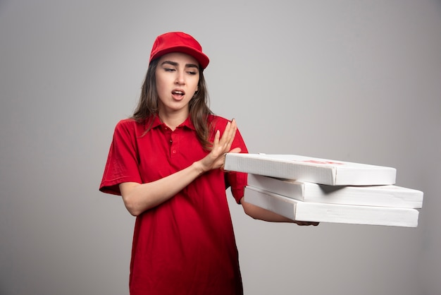 ピザの箱から離れて立っている配達の女性。 無料写真