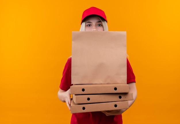 孤立したオレンジ色の壁にピザの箱と紙のポケットを保持している赤いtシャツと帽子を身に着けている配達若い女性 無料写真