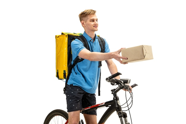 Deliveryman isolated on white studio background. contacless delivery service during quarantine. man delivers food during isolation. safety. professional occupation. copyspace for advertising. Free Photo