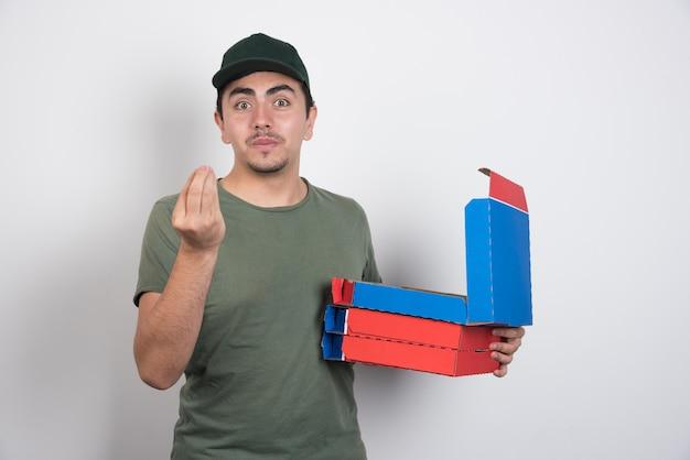 手サインを作り、白い背景にピザの箱を持っている配達員。 無料写真