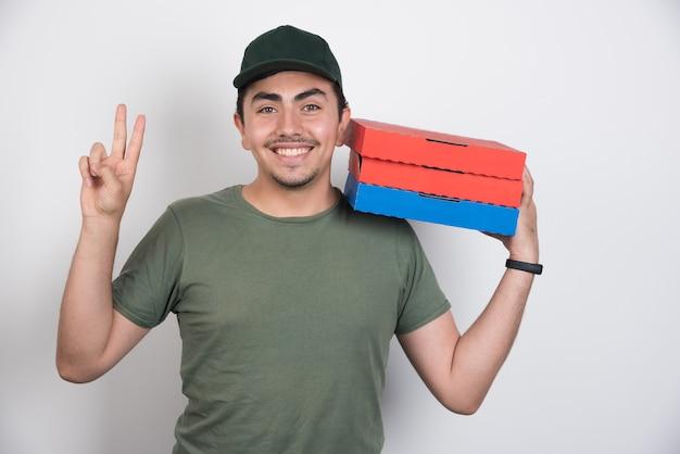 Доставщик, делая знак и держа три коробки пиццы на белом фоне. Бесплатные Фотографии
