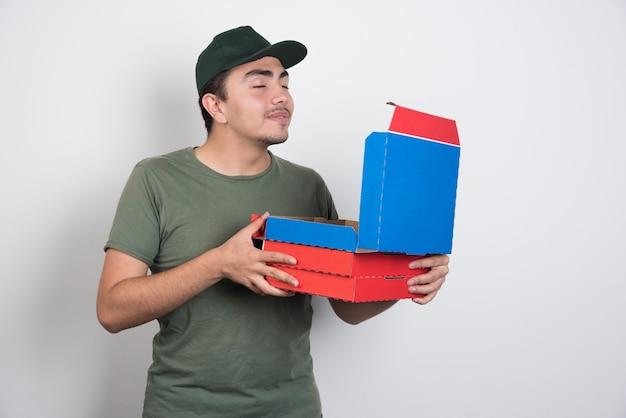 白い背景にピザの匂いを嗅ぐ配達員。 無料写真