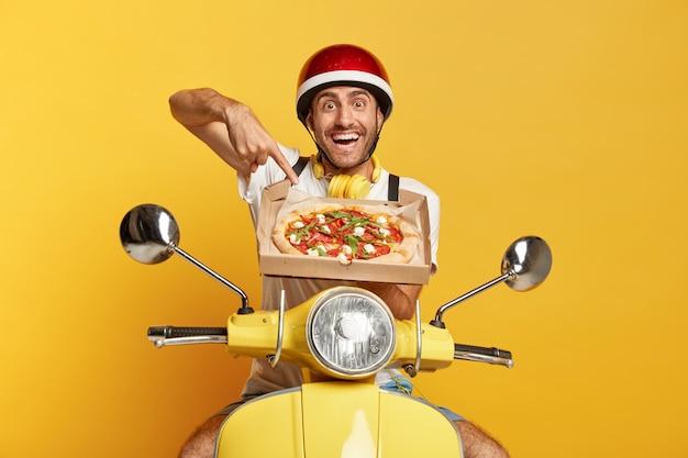 Fattorino con casco guida scooter giallo mentre si tiene la scatola della pizza Foto Gratuite