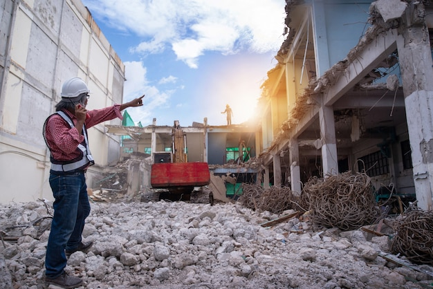 Demolition control supervisor or engineer, walkie-talkie in hand and point finger Premium Photo