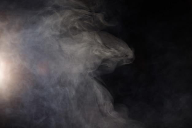 Густые пушистые клубы белого дыма и тумана на черном фоне Premium Фотографии