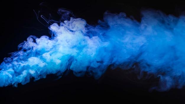 Густые пары абстрактного голубого дыма на темном фоне Premium Фотографии