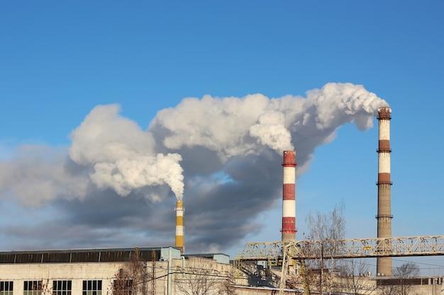 Dense smoke burst from the three factory chimneys. Premium Photo