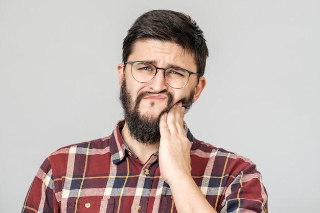 歯科と健康の概念。歯に手を握って気になる魅力的な男の肖像 Premium写真