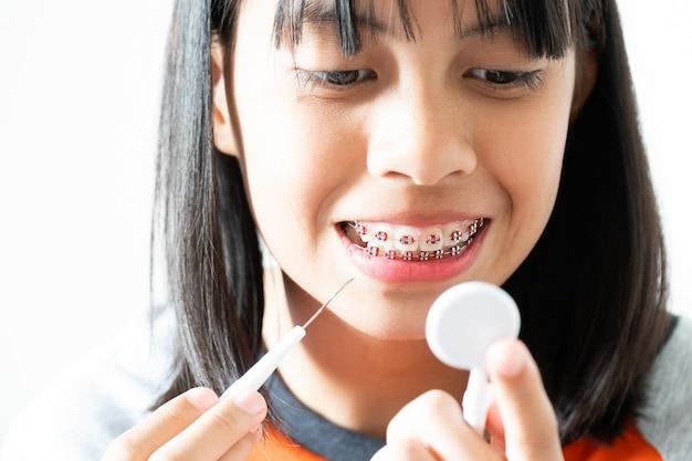 Dental brace girl улыбается и чистит зубы, чувствует себя счастливым и хорошо относится к стоматологу Premium Фотографии