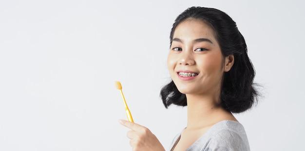 Улыбка девушки-подростка стоматологической скобки, держащая зубную щетку. белые зубы с синими скобами. стоматологическая помощь. азиатская женщина с контактными линзами и ортодонтическими принадлежностями. косметическая стоматология. Premium Фотографии