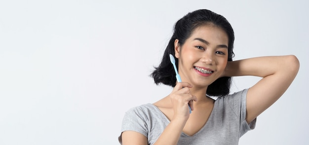 중괄호 치아와 콘택트 렌즈를 착용하는 십대 아시아 여성의 치과 교정기 그녀는 매우 자신감이 넘치고 자랑스럽게 자신을 제시하고 흰 벽에 미소를 지으며 웃고 있습니다. 프리미엄 사진