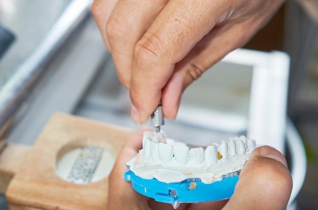 Dental technician using a screwdriver to fix ceramic dental implants in his laboratory Premium Photo