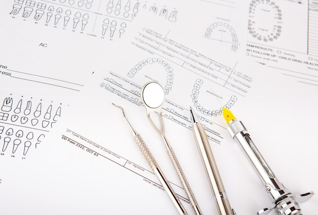 Dental tools and equipment on dental chart Free Photo