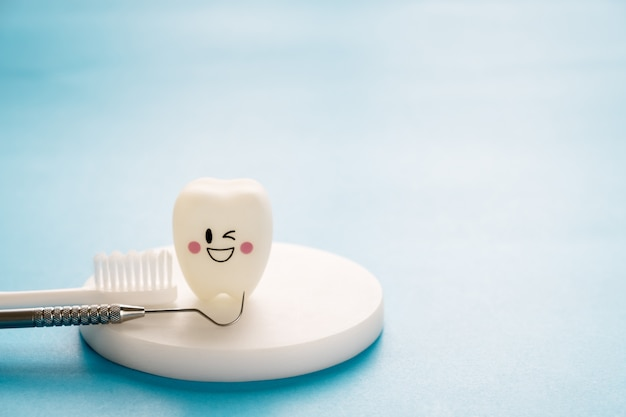 Dental Tools And Smile Teeth Model On Blue Background Premium Photo