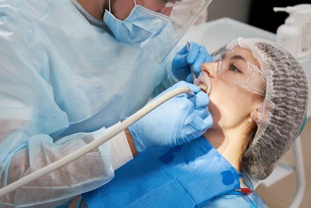 歯科医が歯科用椅子で男性患者に歯をドリルする Premium写真