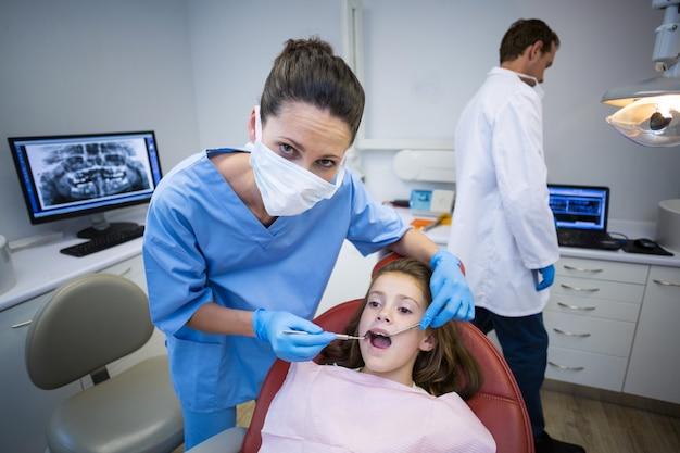 Стоматолог осматривает молодого пациента с инструментами Premium Фотографии
