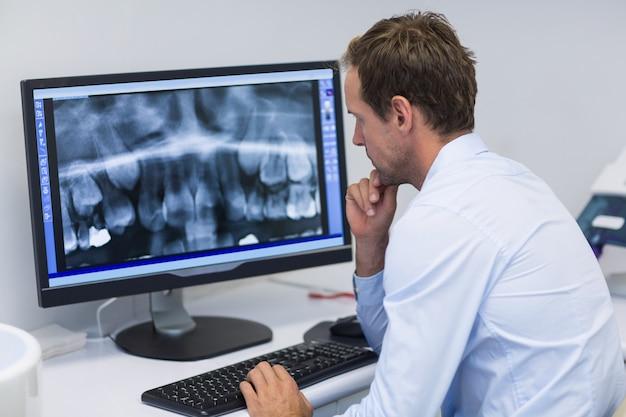 Стоматолог, исследующий рентгеновский снимок на компьютере в стоматологической клинике Premium Фотографии