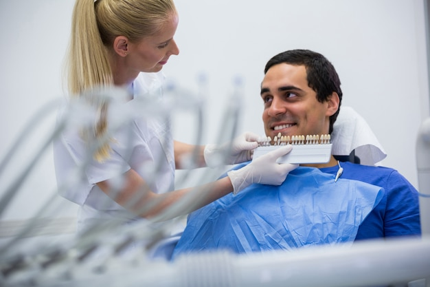 Dentist examining female patient with teeth shades Free Photo