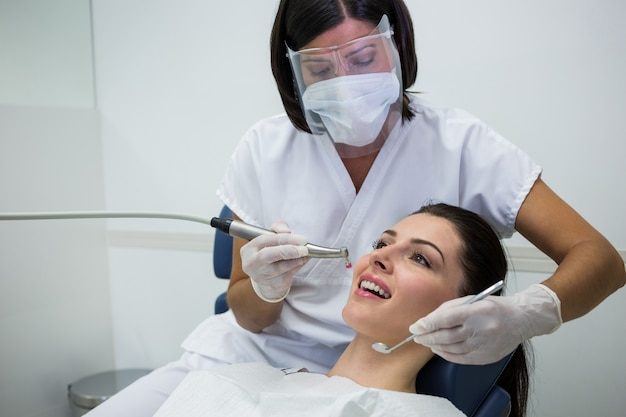Dentist examining a female patient with tools Free Photo