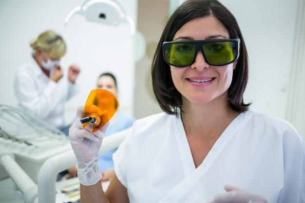 Dentist holding a dental curing ultraviolet light Free Photo