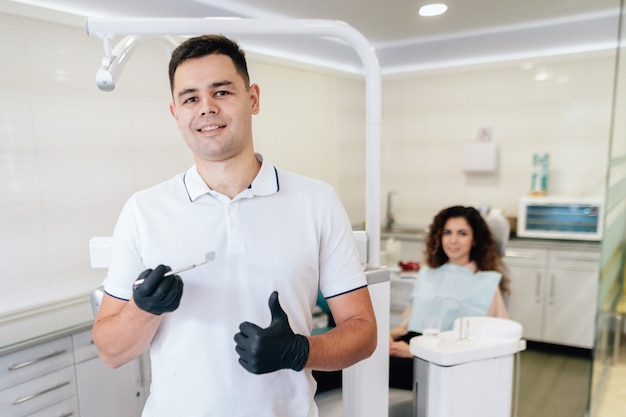 Dentist holding instrument and patient in the office Free Photo