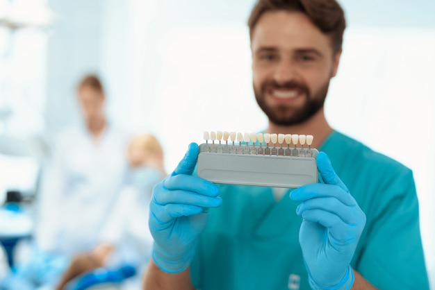 A dentist is posing with a tooth color scale. Premium Photo