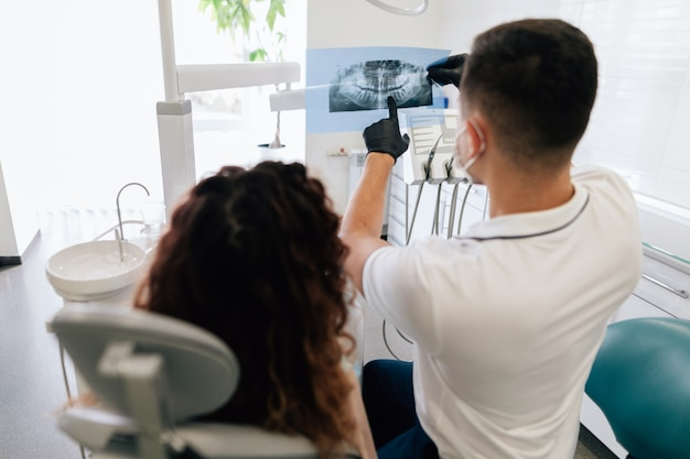 Dentist pointing at radiography with patient Free Photo