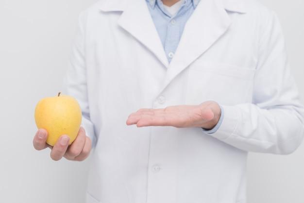 Dentist presenting apple Free Photo