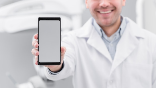 Dentist presenting smartphone Free Photo