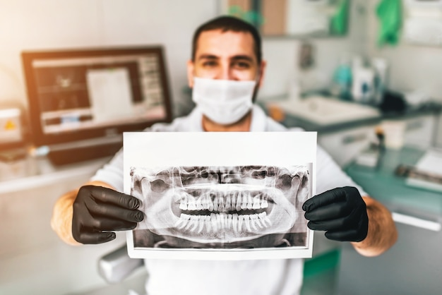 Dentist showing the x-ray of the patient in the dental clinic Premium Photo