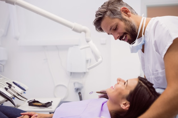 Dentist smiling while examining patient Free Photo