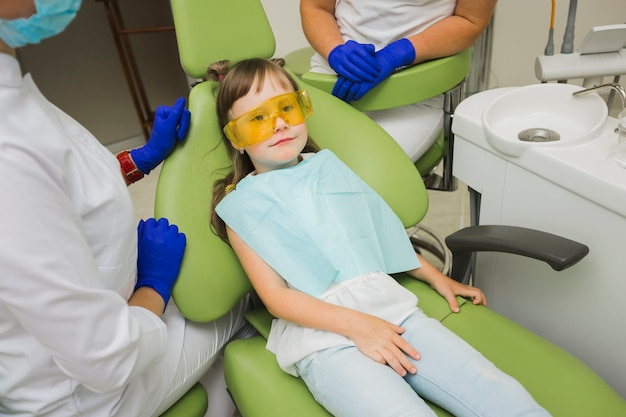 Dentist with girl on chair Free Photo