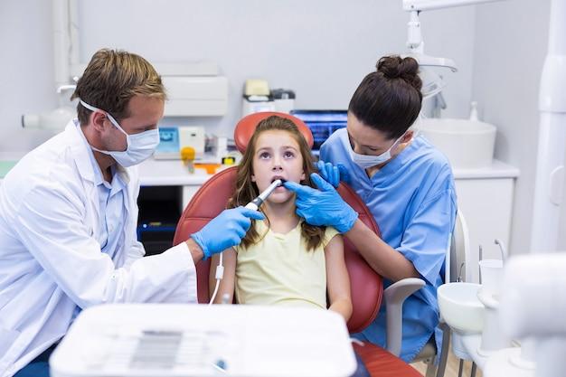 Стоматологи осматривают молодого пациента с инструментами Premium Фотографии