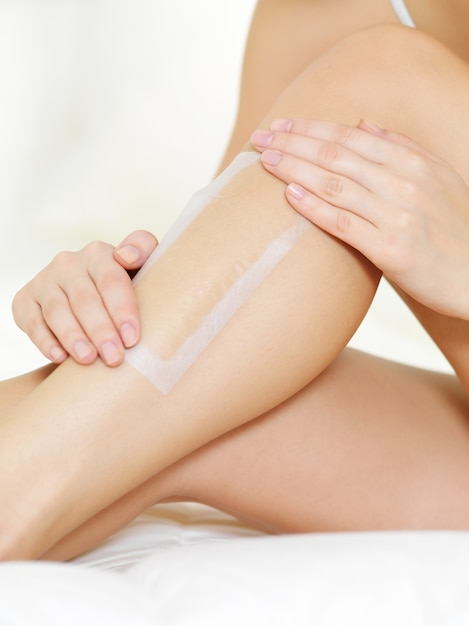 Depilation of female legs by wax Free Photo