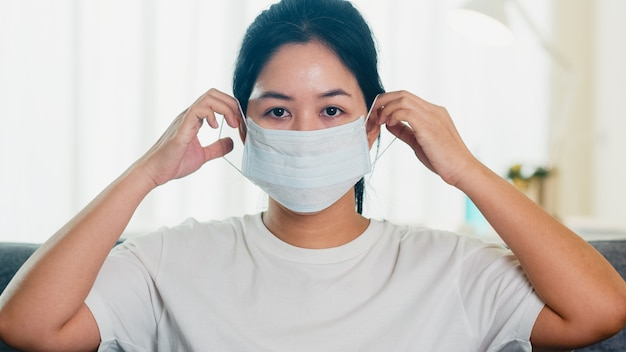 Depressed asian business woman wearing protective mask sitting on sofa in living room at house when social distancing stay at home and self quarantine time, pandemic in china, coronavirus concept. Free Photo