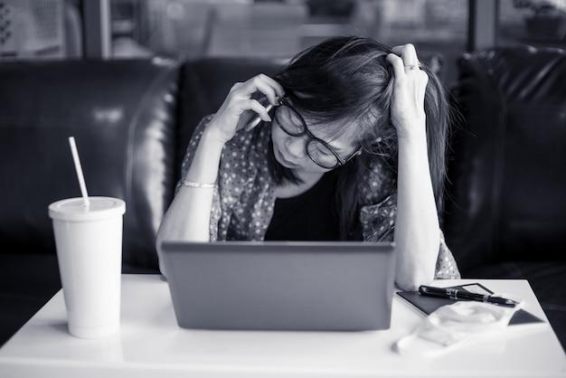 Подавленная азиатская женщина сидит на столе в доме. она работает из дома из-за проблемы с covid19 или коронавирусной вспышкой. черно-белый стиль Premium Фотографии