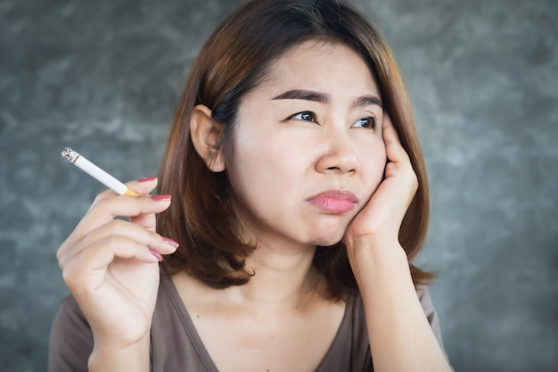Depressed asian woman smoking cigarette with unhappy face Premium Photo
