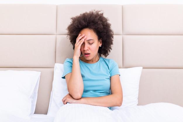 Подавленная черная молодая женщина сидит на диване расстроен, имея личные проблемы Premium Фотографии