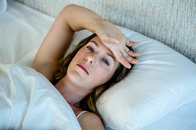 Depressed brunette wwoman lying in bed with her hand across her forehead Premium Photo