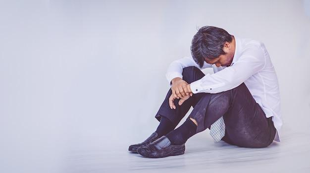 Depressed businessman sitting on the floor Premium Photo