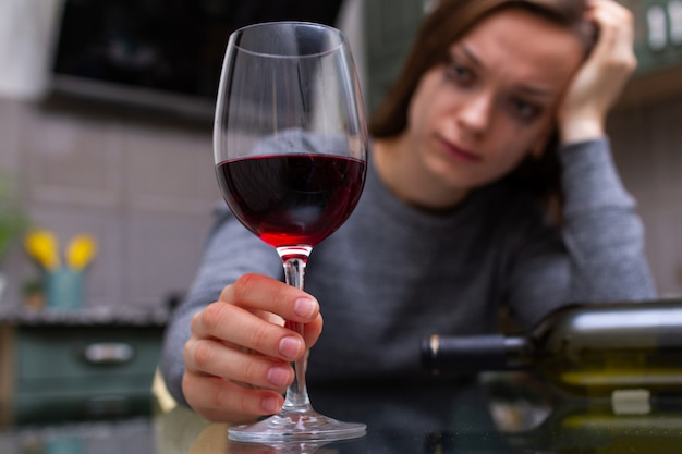 Depressed, divorced crying woman sitting alone in kitchen at home and drinking a glass of red wine because of problems at work and troubles in relationships. social and life problems Premium Photo