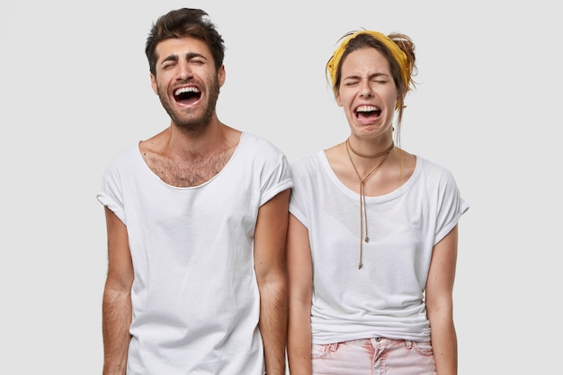 Depressed family couple cry desperately, feel negative emotions, wear white casual t shirt, frown faces in despair, model over  wall, find out tragic news Free Photo
