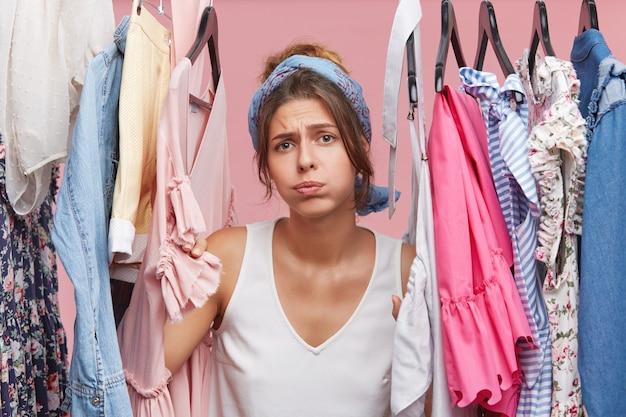 洋服だらけのワードローブラックの近くに立って落ち込んでいる女性。 無料写真