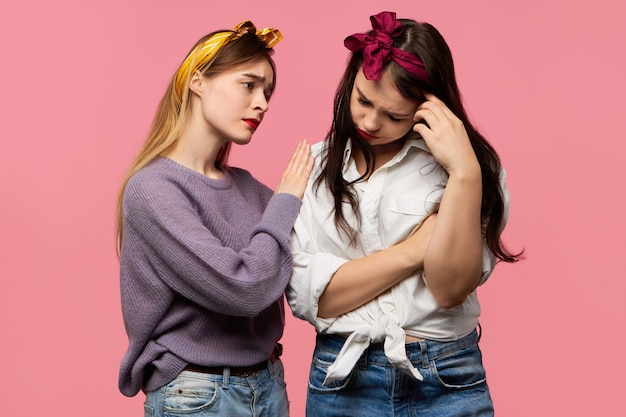 Depressed girl crying because of break up with boyfriend while supportive female friend expressing sympathy, being sorry for her, saying everything will be alright Free Photo